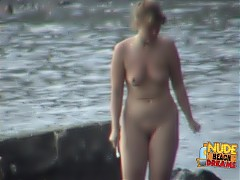 Busty milf walks around naked at the beach