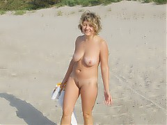 Nudist couple posing for the cameraman at the beach